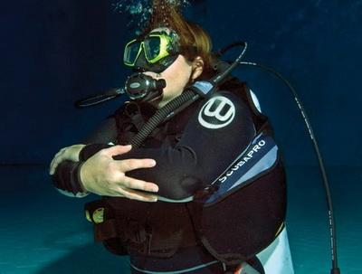Странное дело, я всегда полагал, что шесть метров - это серьезно... На самом деле - всего три движения ластами, и вот уже я трогаю рукой дно бассейна. По правде сказать, для меня это был шок. Ни с чем не сравнимое ощущение от сознания того, что я нахожусь на глубине шести метров, сам дышу под водой! От того, что могу парить, могу ничего не весить, от того, что я легок, что стихия меня приняла... Опять и опять проверяем знаки, еще и еще раз пытаюсь выровнять дыхание, чтобы оно было мерным, глубоким и спокойным. Понимаю, что так, как дышу я, дышать нельзя (слишком волновался и пускал пузыри, как паровоз - облака дыма). Через какое-то время всплываем и обмениваемся впечатлениями. Их у меня через край, выразить и описать это невозможно!      Программа погружения продолжается. Стоя на платформе, осваиваю навыки, положенные каждому дайверу. Первое - вытащить легочник под водой, правильно его вставить и начать дыхание, второе - освободить маску от воды. Первое получается быстро, со вторым приходится помучиться. Почему-то очень неприятно выдыхать носом под водой. Видимо, потому, что очень хочется вдохнуть, а нельзя. На маску уходит минут пять, после чего опять уходим на дно. И вот тут оказывается, что у инструктора есть для меня сюрприз. Не знаю, научили ли его представители IAHD, или это было наитие, но идея была гениальной. После того, как мы проплываем пару метров над дном, инструктор ставит мои руки на межплиточные швы. Я сам, признаться, думал об этом или чем-то подобном, но не успел обсудить это с инструктором. Простота и оригинальность идеи поражает, ведь межплиточные швы прямые, и по ним легко ориентироваться. Плыву уже практически сам, инструктор только слегка касается пальцами моего плеча. Я показываю «ОК» и не знаю, как показать ему тысячу и тысячу «ОК», чтобы выразить свой восторг. Я парю надо дном, я свободен, почти един с водой! Через какое-то время поднимаемся на платформу. Очень не хотелось всплывать, но своей очереди ждал следующий.      Что дальше? А дальш
